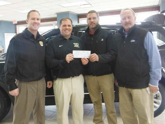 Pierson Ford recently presented a check for $5,000 to Presentation College for the college's participation in a test drive fundraising event in October. From left are Kelly Krausz, general sales manager; PC head football coach Andy Carr; Seth Anderson, sales consultant; and Larry Twiss, sales consultant.