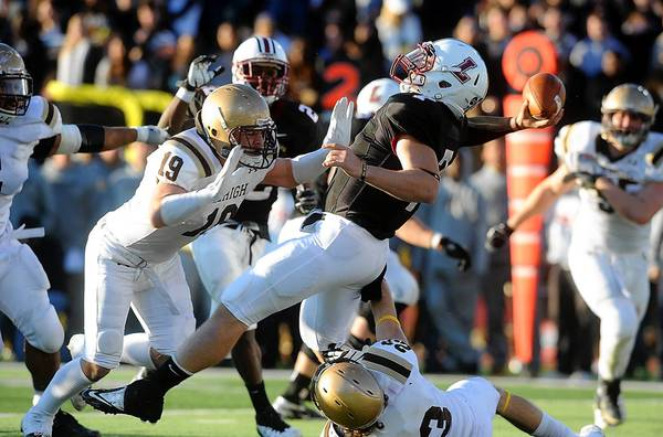 Lehigh's Sam Loughery (left) and Tyler Ward (bottom right, put pressure on Lafayette quarterback Andrew Shoop.