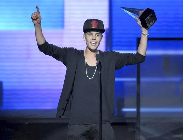 "Justin Bieber accepts the award for favorite album, pop/rock, for ""Believe"" at the American Music Awards on Sunday in Los Angeles."