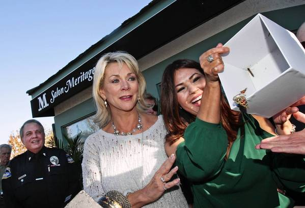 Sandi Fanin and Irma Acosta, co-owners of Salon Meritage, set butterflies free Sunday as they celebrate the reopening of the salon.