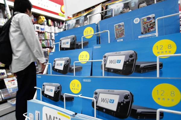 A customer walks past brochures advertising Nintendo Co.'s Wii U game console at an electronics store in Tokyo, Japan, on Wednesday, Oct. 24, 2012. The Wii U is now on sale in the U.S.