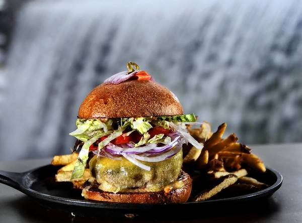 A prime beef cheeseburger with cheddar, onions, lettuce, tomato and duck fat fries at the Millwright Tavern. The signature waterfall is in the background.