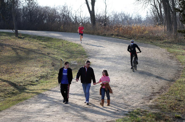 "Duncan, center, and Maria Greathead, of Hawthorne Woods, walk with their son Donald, left, on the hilly ""lighted trail"" segment of the Millennium Trail at Lakewood Forest Preserve off Fairfield Road and Rt. 176 in Wauconda."