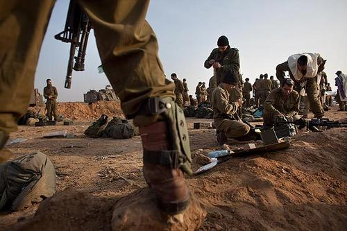 Israeli soldiers prepare weapons in a deployment area on Monday on Israel's border with the Gaza Strip.