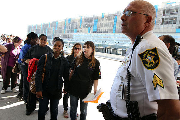 Cami Acceus with Organize Now, left, and JoEllen Chernow with Common good, center, debate with a Broward Sheriff Office deputy their right to conduct a silent, walking protest for airport workers through all four terminals at the Fort Lauderdale-Hollywood International Airport to protest low wages. An official with Broward County allowed the protest to continue.