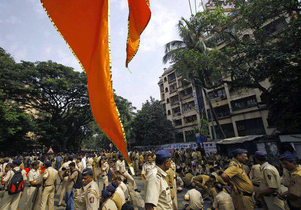 A flag of the Shiv Sena party hangs in the foreground as Indian policemen are deployed outside the residence of Hindu nationalist politician Balasaheb Thackeray in Mumbai.