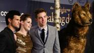 "Robert Pattinson (R), Kristen Stewart (C) and Taylor Lautner pose for pictures before the German premiere of ""The Twilight Saga: Breaking Dawn Part 2"""