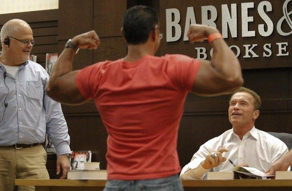 A man shows his muscles to former California Gov. Arnold Schwarzenegger during a book signing.