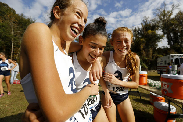 St. Thomas Aquinas teammates Megan Schloss, left, Christina Kalis and Brianna Rischar embrace after hearing they won the team title for the Class 4A FHSAA state cross country championships in Tallahassee.