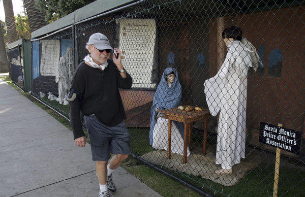 A man walks past two of the traditional Nativity scenes along Ocean Avenue at Palisades Park in Santa Monica last year.
