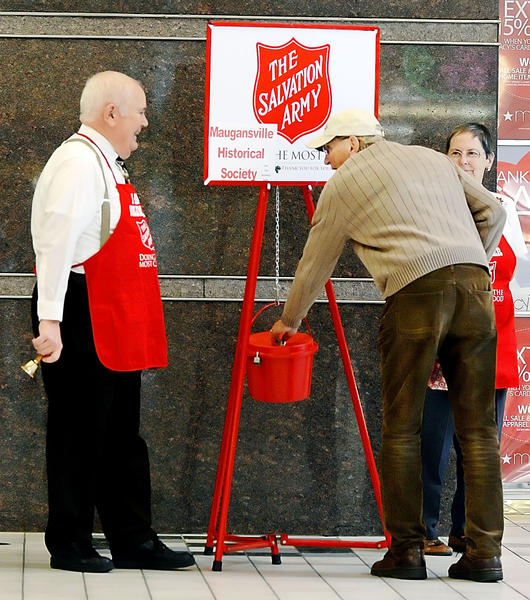 Howard Weaver of Williamsport places a contribution into a Salvation Army kettle being tended by bell ringers Robert and Virginia Walton of Maugansville Monday at the Valley Mall.