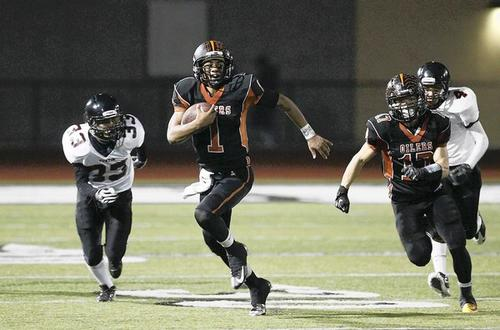 Huntington Beach's Kai Ross scrambles upfield on a quarterback keeper against Tustin during a CIF Southern Section playoff game at Huntington Beach High School on Friday.