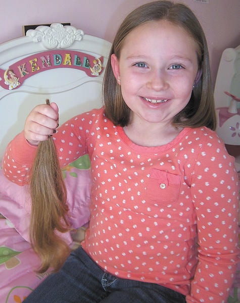 Kendall Whittington holds the ponytail she donated to the Locks of Love program.