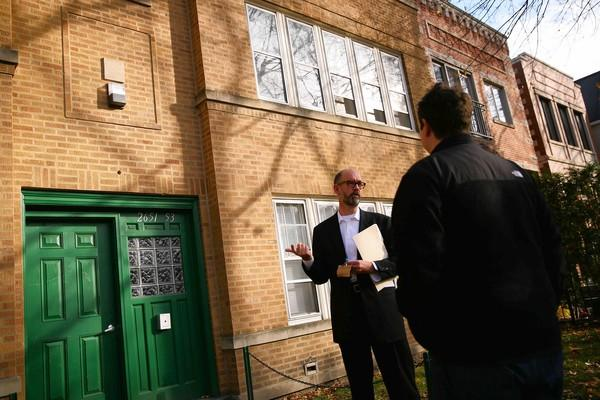 "Real estate agent Robert John Anderson shows an apartment building to potential buyers who may turn it into condos in the Lincoln Park area. ""I was running around Saturday and Sunday and bumping into the same brokers and they all looked tired and busy,"" he said. ""It's exciting."""