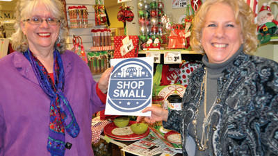 "Somerset Inc. Executive Director Stephanie Williams and merchant committee co-chairwoman Ramona Huston, of Somerset Drug, hold up a ""Shop Small"" promotional sign in support of Small Business Saturday."