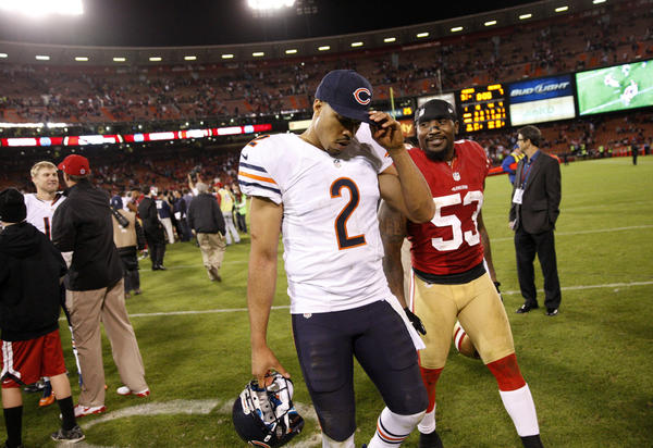 Bears quarterback Jason Campbell walks off the field beside a smiling 49ers linebacker NaVorro Bowman.