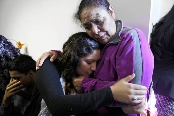 Natalie de la Trinidad hugs Sofia de la Trinidad, right, the mother of Jose de la Trinidad, who was shot and killed Nov. 10.