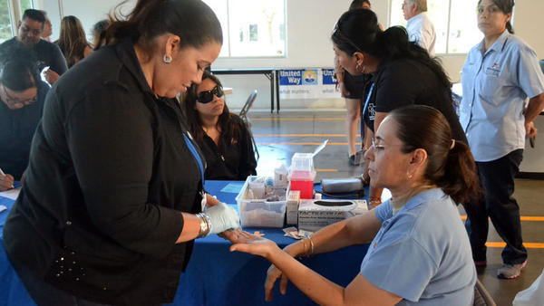 Teve Sandoval (right) gets her blood checked by Elva King, a community service worker for Clinicas de Salud del Pueblo Inc., at the diabetes health awareness fair Monday at the UPS building in Calexico.