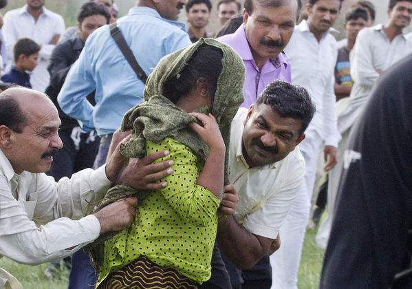 In this Sept. 8 file photo, a Pakistani police officer and a Christian volunteer escort a young Christian girl accused of blasphemy toward a helicopter following her release from central prison near Rawalpindi, Pakistan. A defense lawyer said Tuesday that a Pakistani court has acquitted the girl accused of burning pages from a Koran.