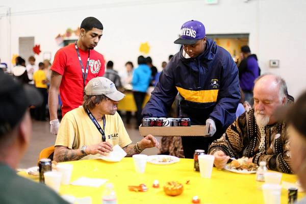Phil Nouse, left, of Laurel gets a soda from Howard County NAACP Youth Council's Takim Herring-Hall, 14, of Columbia, while they feed the homeless at Ridgely Run Community Center in Jessup Nov. 18.