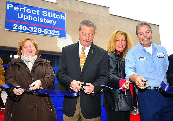 Cutting the ribbon Nov. 15 at the refurbished Perfect Stitch Upholstery building at 60 E. Washington St. in Hagerstown are, from left, Maryland Department of Business and Economic Development representative Vickie Swink, Hagerstown Mayor Robert E. Bruchey II, Michelle Cress and John Cress.
