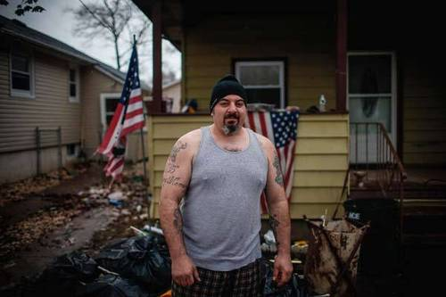 Anthony Morotto poses for a photograph in front of the home he rents in New Dorp Beach, Staten Island. At the height of Hurricane Sandy, Morotto heard screaming from behind his home, one of only a handful in the area with a second story. He tied a rope to his waist and pulled three neighbors from the flood in through his second story window. At least 23 people died on Staten Island mostly from drowning in storm surge flooding.