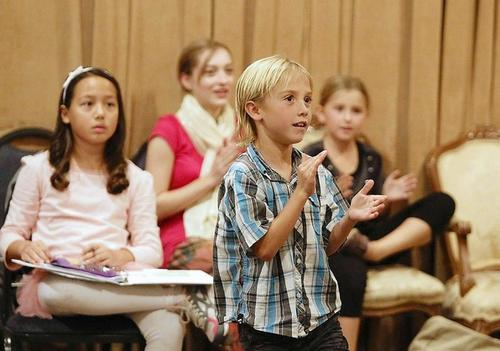 "Cast member Zacharias Harris, who plays Tiny Tim, claps to a song as he reherses a scene for ""A Christmas Carol"" at South Coast Repertory."