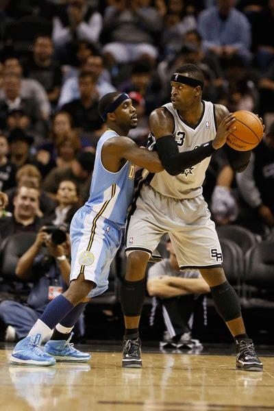 San Antonio Spurs forward Stephen Jackson (right) is defended by Denver Nuggets guard Ty Lawson (left) during the second half at the AT&T Center.