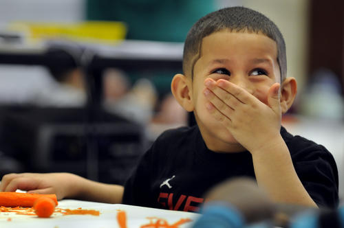 Nathanael Hernandez, 6, (cq) laughs as the carrot he was cutting in class went flying off the table.
