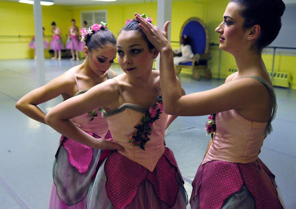 Candice Quarella (R) fixes Abbie Holt's (C) hair as Alex Nelson (L) makes sure her costume is secured as they wait for rehearsal of the Nutcracker to begin at the Connecticut Concert Ballet's studio in Manchester.