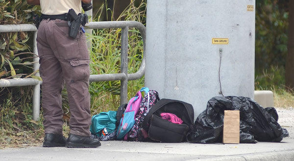 A police investigator photographs school backpacks taken off a school bus after a child was shot in Homestead, Fla.