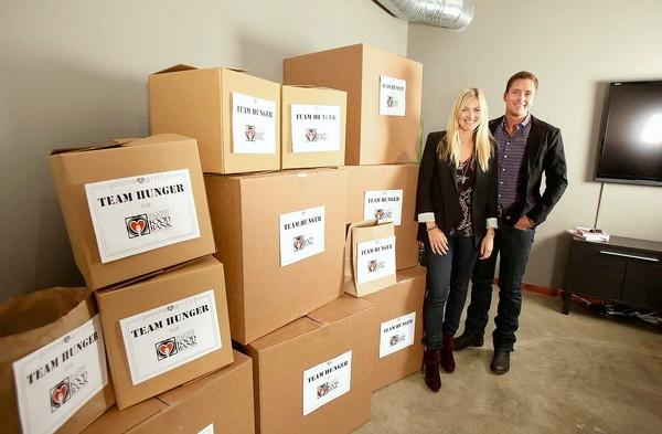 Gorjana and Jason Griffin Reidel stand next to the last boxes from Team Hunger, a food drive that gathered 10,857 pounds of goods for the Second Harvest Food Bank of Orange County.