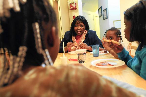 Flecia Thomas talks with the kids during a family dinner at her home in Crystal Lake.