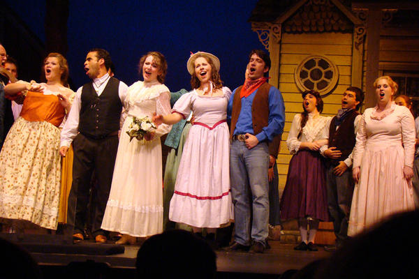 "From left, Rebecca Feibel (as Aunt Eller), Ben Harris (Curly), Emily Mudd (Laurey), Nicole Bowen (Ado Annie) and Nathan Bowen (Will Parker), with ensemble players to the right, sing during 2nd Star's production of ""Oklahoma."""