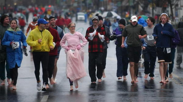 "Despite cold, rainy conditions at the Manchester Road Race in November 2006, a group of runners honored the late Charley ""Doc"" Robbins before the race by running barefoot down Main Street. Charley Robbins ran the race (and won it multiple times) barefoot for many years. Running legend and multiple winner Amby Burfoot is in the center in red, carrying his shoes. He's joined by Bekkie Wright of the Silk City Stridders, in pink, and others."