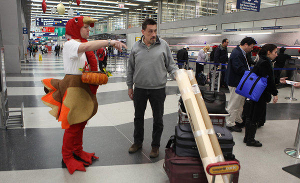 Portraying a holiday turkey for American Airlines, Danney Sweeney gives out suckers to travelers heading out for the Thanksgiving holidays, at terminal three at O'Hare International Airport on Nov. 23, 2011.