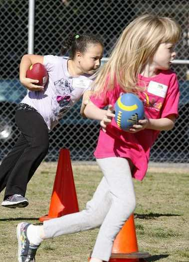 Alena Tyler, 7, and Anna Fitzgerald, 7, turn the corner in a football relay race student teams for USC against UCLA, at McKinley Elementary School in Burbank on Monday, November 19, 2012.