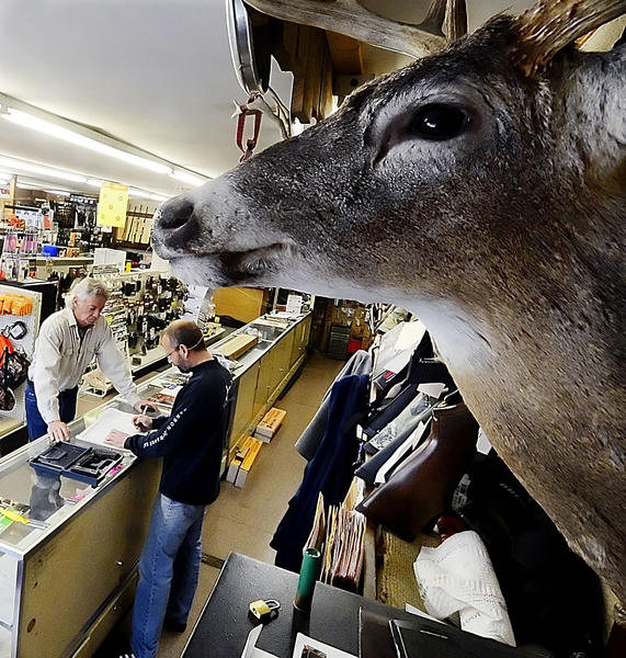 Tim Stahl, right, owner of Keystone Sporting Goods Inc. in Hagerstown, registers a gun to a customer on Tuesday. The store has been busy helping hunters prepare for the start of the Maryland's firearm deer hunting season on Saturday.