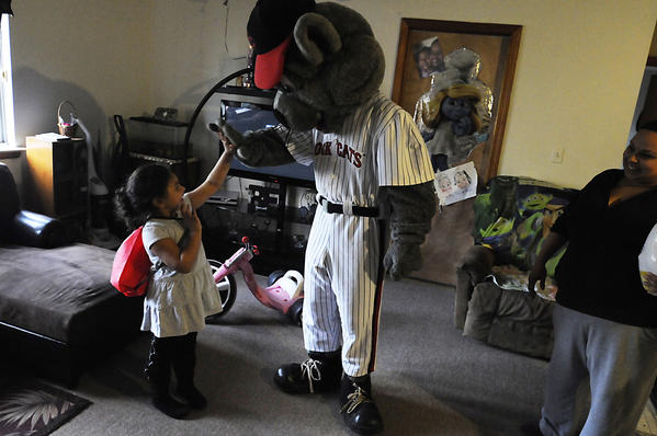 Natalie Rivera, 5, gives Rocky, the mascot for the New Britain Rock Cats the high five after he delivered Thanksgiving dinner to her home in New Britain Tuesday. At right is Natalie's moter, Elizabeth Rivera. The Rock Cats delivered donated non-perishbale food items, holiday food baskets and Thanksgiving turkeys to 10 local families in need in New Britain Tuesday. This is the 13th consecutive year that the Rock Cats made  donations to assist their neighbors in need, with the food coming from Stew Leonard's of Newington, Trader Joe's of West Hartford and from Rock Cat fans