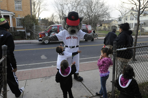 Jiovani Lopez, 5, of New Britain goes to embrace Rocky, the mascot for the New Britain Rock Cats, with turkey in hand,  who brought Thanksgiving dinner to a family on Washington Street in New Britain Tuesday. The Rock Cats delivered donated non-perishbale food items, holiday food baskets and Thanksgiving turkeys to 10 families in need in New Britain Tuesday. This is the 13th consecutive year that the Rock Cats made  donations to assist their neighbors in need, with the food coming from Stew Leonard's of Newington, Trader Joe's of West Hartford and from Rock Cat fans.