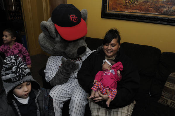 Lillian Rivera holds her granddaughter Aliala DeJesus, 1 month, with Rocky, the mascot for the New Britain Rock Cats Tuesday at her home in New Britain.