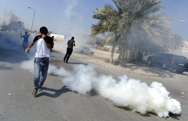 Protesters scramble as police fire tear gas north of the Bahraini capital of Manama this month.