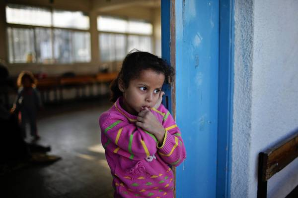 A displaced Palestinian girl, who fled her home amid the conflict between Israel and Hamas, stands Tuesday near a classroom while staying at a U.N.-run school in Gaza City.