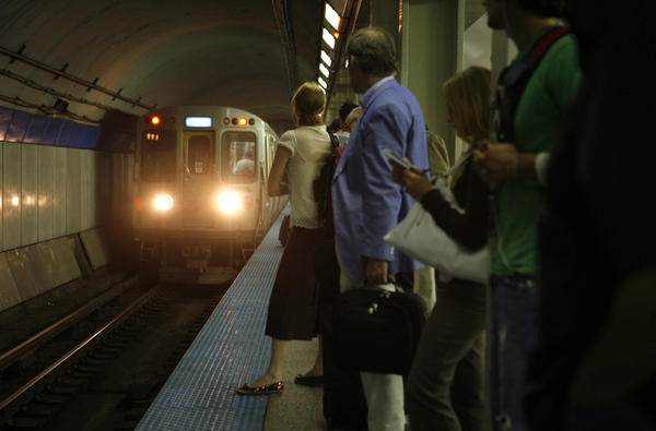 Commuters wait for an O'Hare-bound train at the Thompson Center station on the CTA Blue Line.