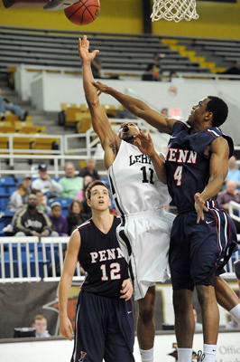 Lehigh's Mackey McKnight (center) drives to the basket in between Penn's Fran Dougherty (left) and Jamal Lewis (right) during the consolation round of the NIT tournament at Stabler Arena Tuesday night.