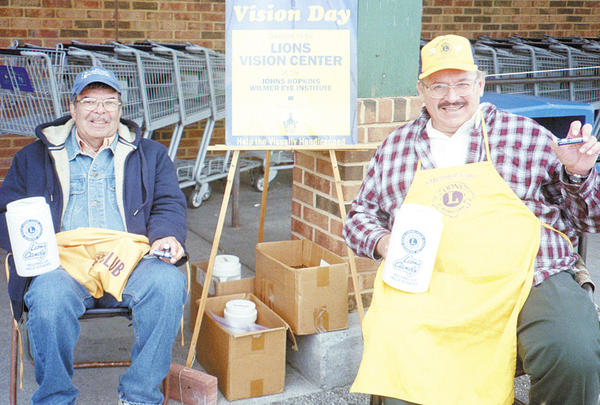 Smithsburg Lions Club members George Souders, left, and Jeff Weaver collect donations for the Wilmer Eye Institute.