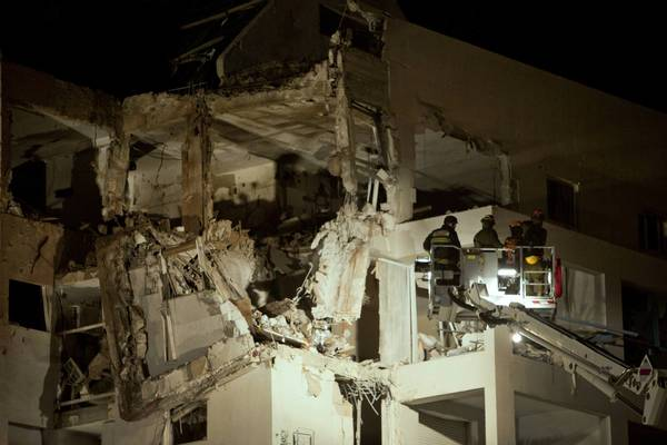 Israeli rescue workers inspect a residential building in Rishon Lezion that was hit by a rocket from the Gaza Strip. The death toll rose on both sides in the Hamas-Israel fighting.