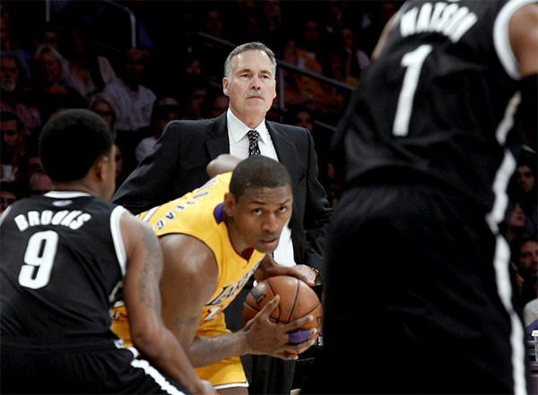 Mike D'Antoni watches his team on the offensive end of the floor while Metta World Peace maneuvers with the ball.