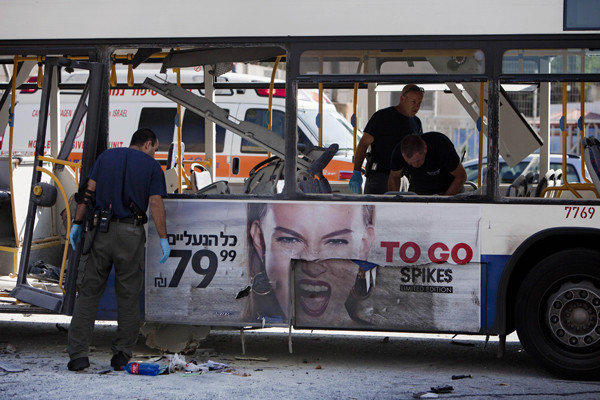 Police officers examine a bus targeted in a bombing in Tel Aviv.
