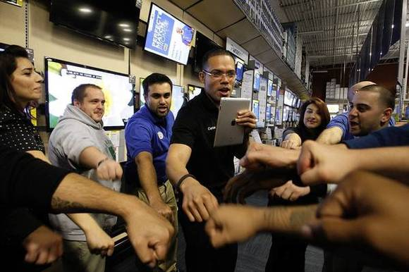 Carlos Portillo, center, leads a cheer in preparing fellow employees at Best Buy's Burbank store for Black Friday.